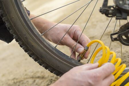 A person inflates a Bicycle wheel with compressed air. Soft focus. Shallow depth of field. Close up view.