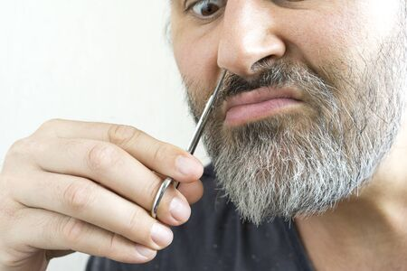 A bearded man cuts his nose hair with a pair of scissors. His face showed a clear determination to endure this procedure. Close-up view. Zdjęcie Seryjne