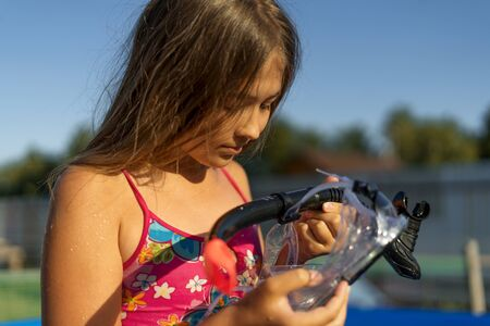 Cute girl in the pool is going to wear a mask and snorkel for scuba diving. She looks at it doubtfully. Banque d'images