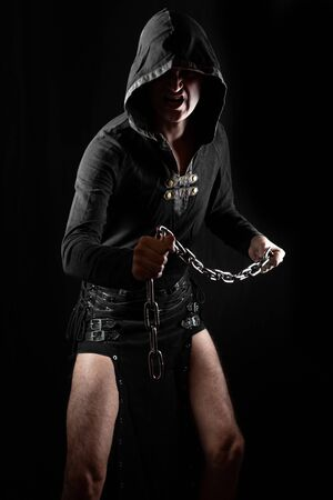 Young man posing in hooded gothic clothes with chain and screaming. Royalty free stock photo. Фото со стока