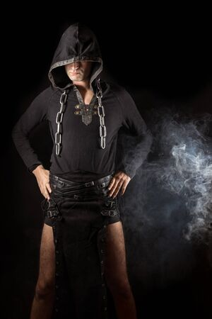 Young man posing in hooded gothic clothes with chain around neck next to smoke. Royalty free stock photo.