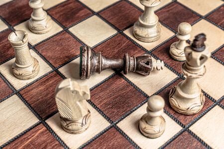 Chess board with black king surrendered to overwhelming force of white chess pieces. Royalty free stock photo.