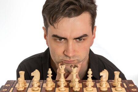 Male chess player contemplating his first move in front of white background. Royalty free stock photo.