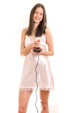 Attractive young brunette woman wearing a pink nightgown, holding a joystick smiling. Royalty free stock photo.
