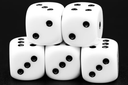 Macro closeup of arranged white dice in front of dark background. Royalty free stock photo.