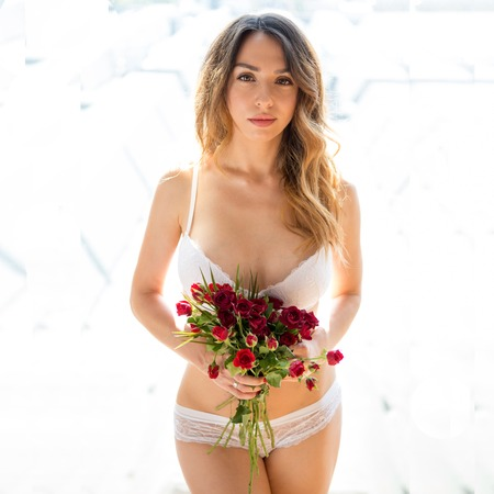 girl standing in underwear with flowers, flirting