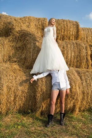 the bride stands over the bridegroom he is in his underpants under the dress of the bride