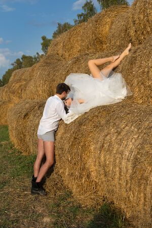the bride is lying on the hay