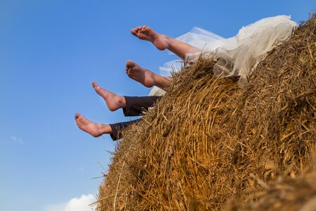 feet of the bride and groom stick out of a stack of straw