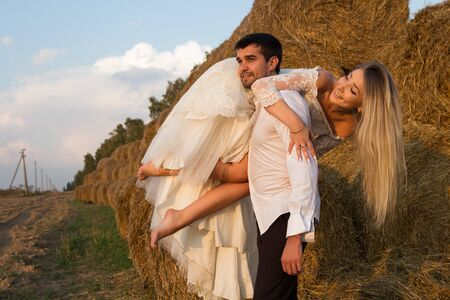 groom carries bride on shoulder along haystack