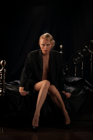 sexy blonde sitting on a bed in a black background