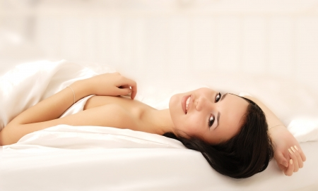 woman lying on the bed and smiling photo