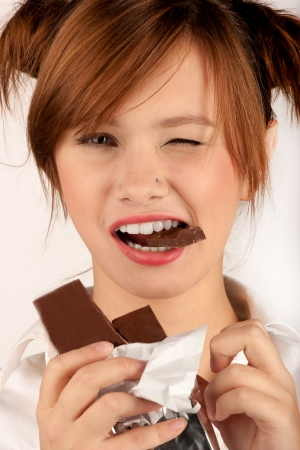 woman holding bite of chocolate