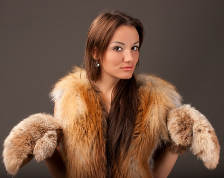 portrait of a young woman with a fur vest mittens