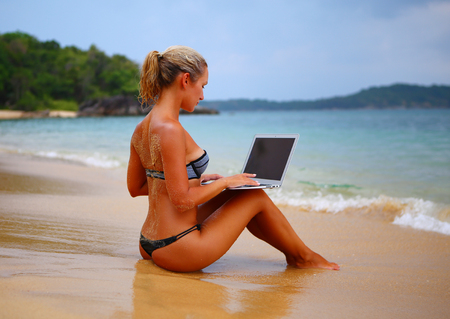 Young woman freelancer using laptop on the beach in Phuket, Thailand. Hipster girl browsing Internet on a noutbook, texting and communicating outdoors. Travel concept Stock Photo