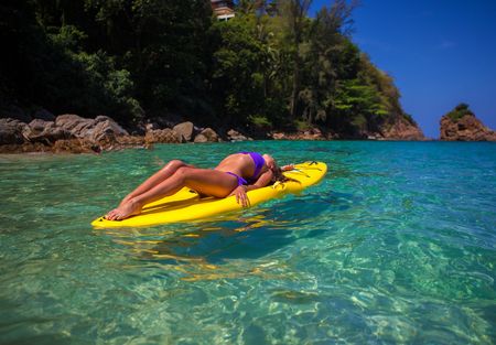 A girl on a kayak (SUP board) in the sea, sailing between fishing boats in Thailand