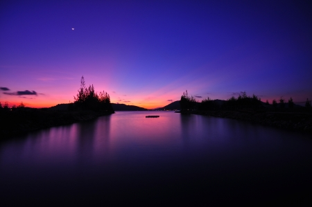 Purple sunset with with rays plus little moon photo