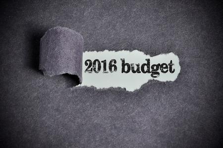money matters: 2016 budget  word under torn black sugar paper Stock Photo
