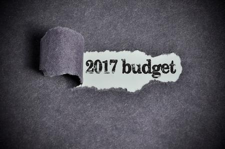 2017 budget  word under torn black sugar paper