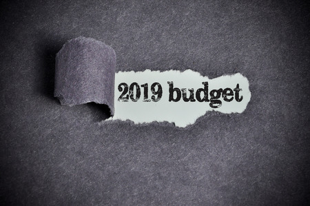 money matters: 2019 budget  word under torn black sugar paper