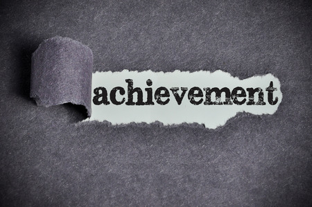 achievement  word under torn black sugar paper