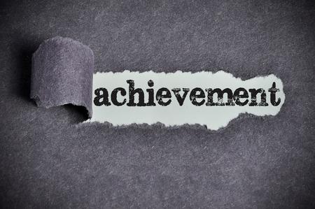 achievement  word under torn black sugar paper