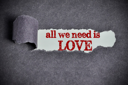 all we need is love  word under torn black sugar paper Archivio Fotografico