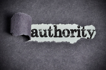 authority  word under torn black sugar paper Stock Photo