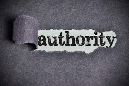 autoridad: palabra autoridad en virtud de papel de az�car negro desgarrado Foto de archivo