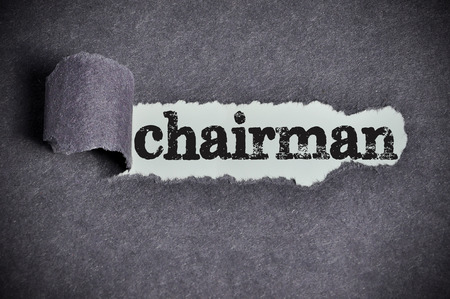 the chairman: chairman  word under torn black sugar paper Stock Photo