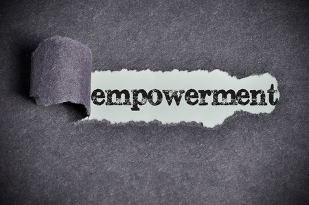 empowerment  word under torn black sugar paper