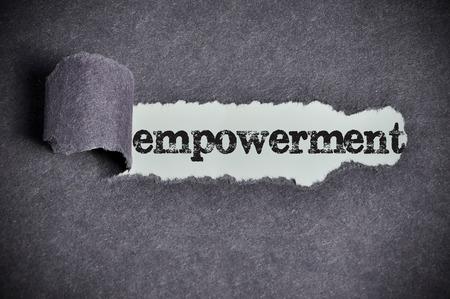 empowerment  word under torn black sugar paper