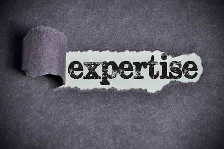 expertise: expertise  word under torn black sugar paper Stock Photo