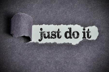 just do it  word under torn black sugar paper Archivio Fotografico