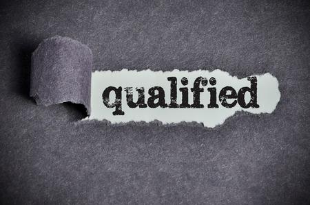 qualified: qualified  word under torn black sugar paper Stock Photo