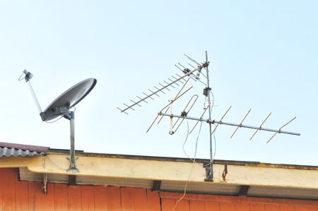 telecast: Satellite dish and tv antenna at the roof. Stock Photo