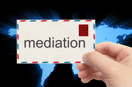 mediation: hand holding envelope with mediation word on world background.
