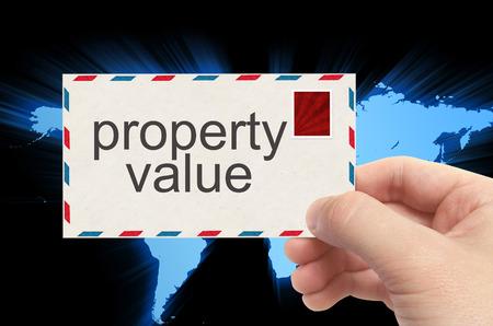 finer: mano que sostiene el sobre con la palabra valor de la propiedad en el fondo mundo.