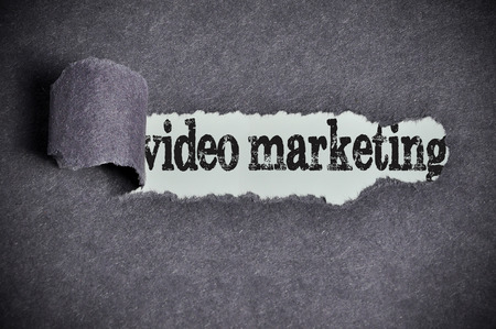 찢어진 된 검은 설탕 종이 아래 비디오 마케팅 단어입니다.