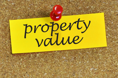finer: property value word on notepaper with cork background. Stock Photo