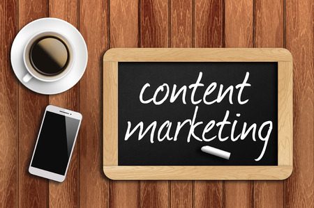 coffee, phone and chalkboard with content marketing words. Archivio Fotografico