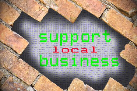 local business: Hole In Brick Wall With support local business Word.