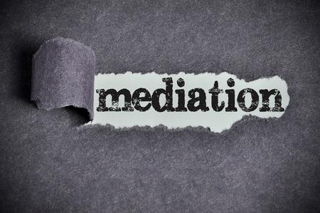 mediate: mediation word under torn black sugar paper. Stock Photo