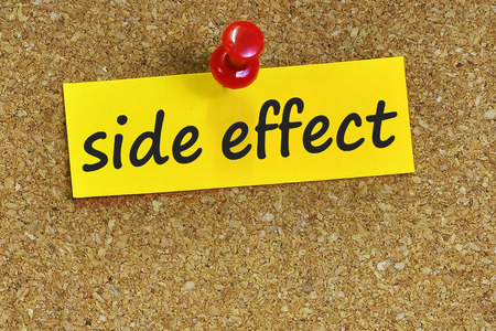 side effect: side effect  word on notes paper with cork background.