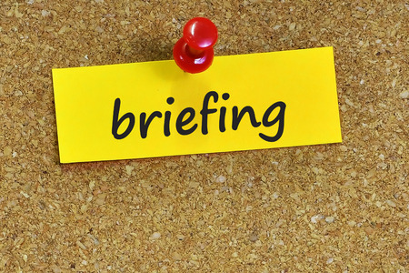 briefing: briefing  word on notes paper with cork background.