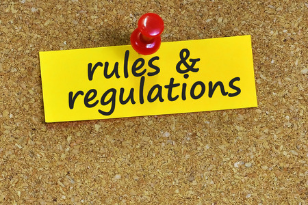 rules & regulations  word on notes paper with cork background.