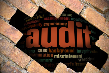 provide information: Hole at the brick wall with audit word cloud inside. Stock Photo