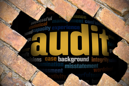 Hole at the brick wall with audit word cloud inside. Stock Photo