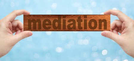 mediator: The Hands holding a wood engrave with word mediation with bokeh background