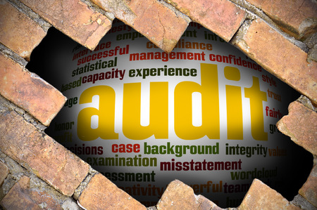 must: Hole at the brick wall with audit word cloud inside. Stock Photo